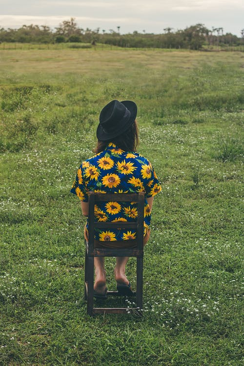 Anonymous woman sitting on chair in field