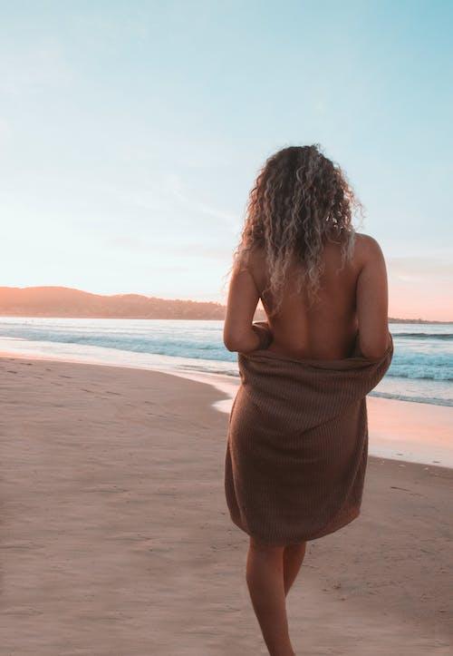 Topless Woman Standing on Beach