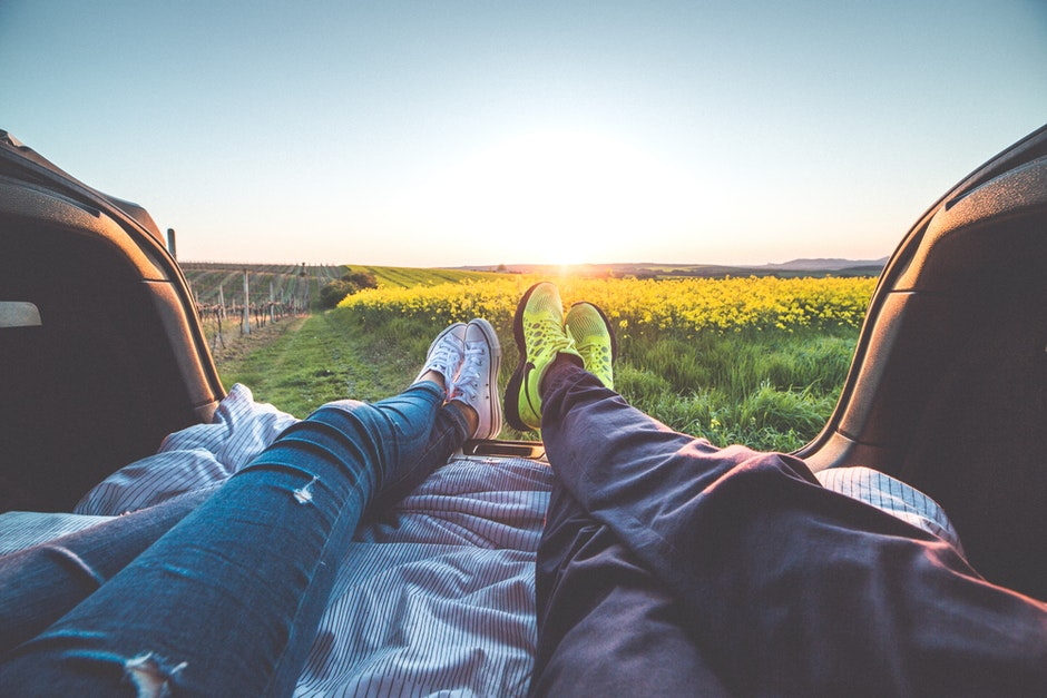 Image of two peoples legs as they spread out relaxing in the back of a car as the sunsets in the background