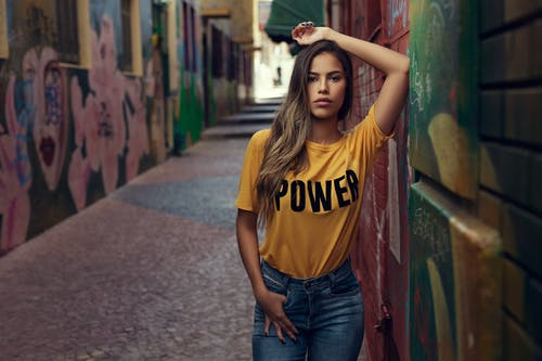 Woman Wearing Brown and Black Power Printed Shirt Leaning on Wall