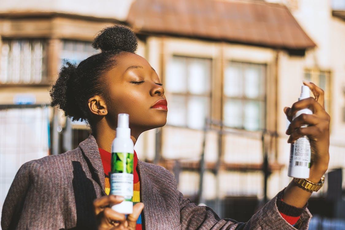 Woman Holding Two White Spray Bottles
