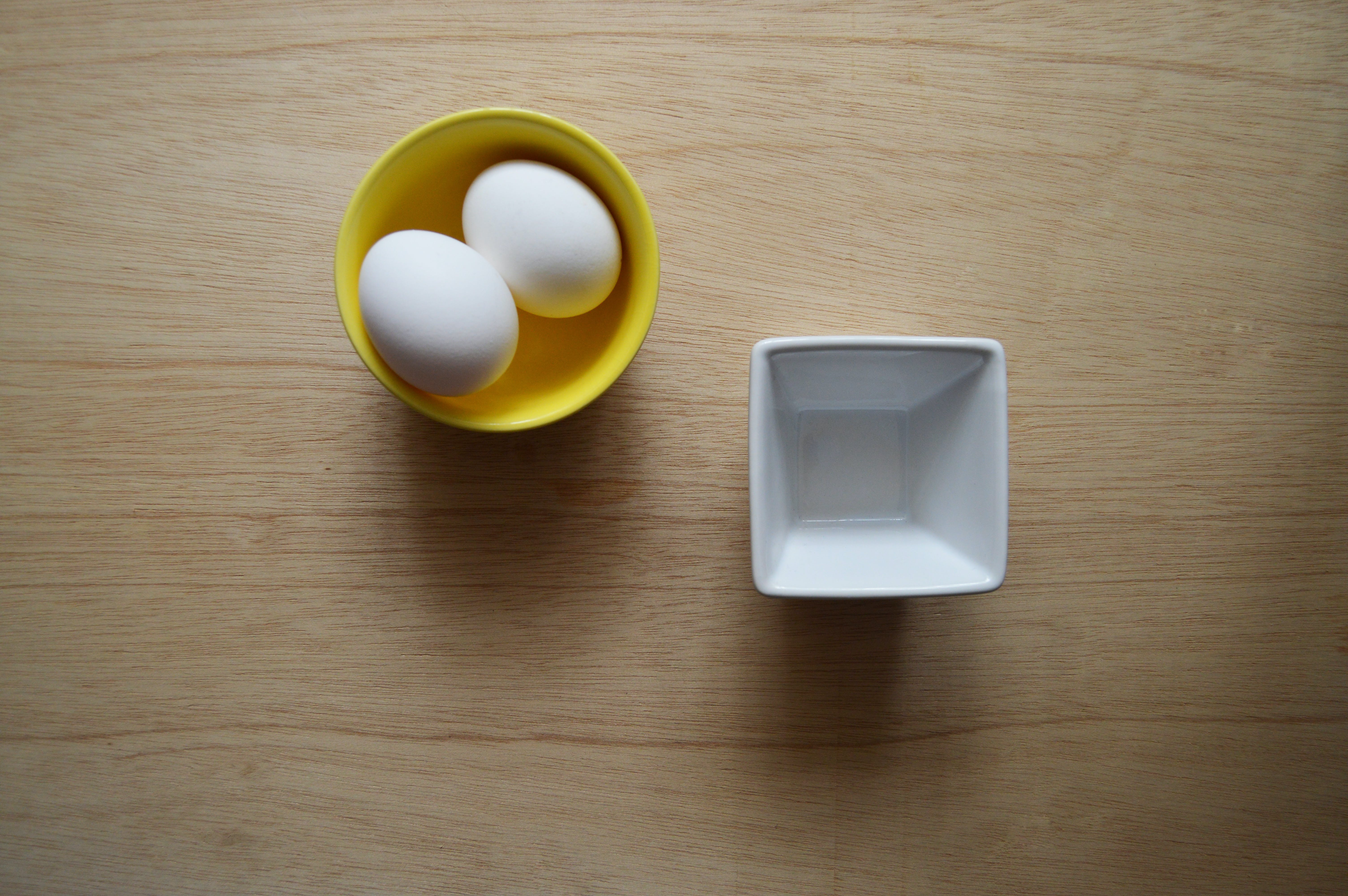 Two White Eggs in Yellow Ceramic Bowl