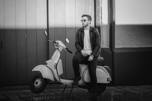 Grayscale Photo of Man Sitting on Motor Scooter Posing