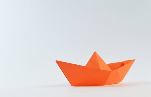 Orange Paper Boat on White Surface