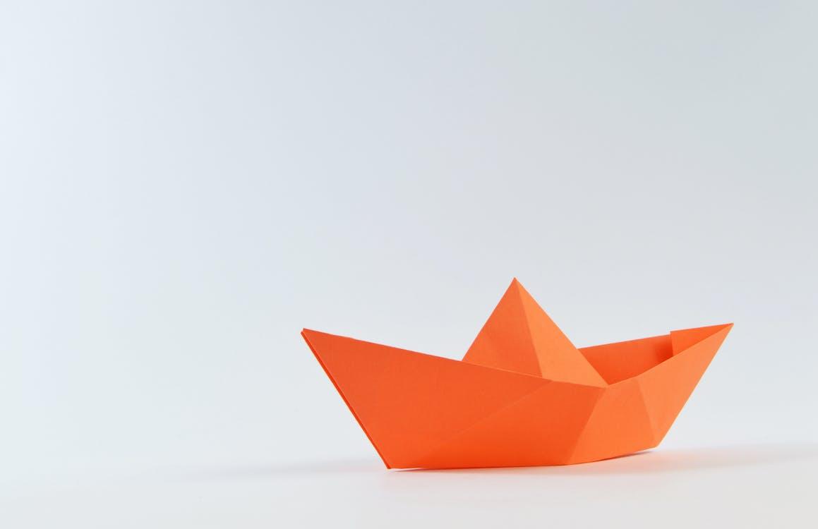 Orange Paper Boat on White Surface