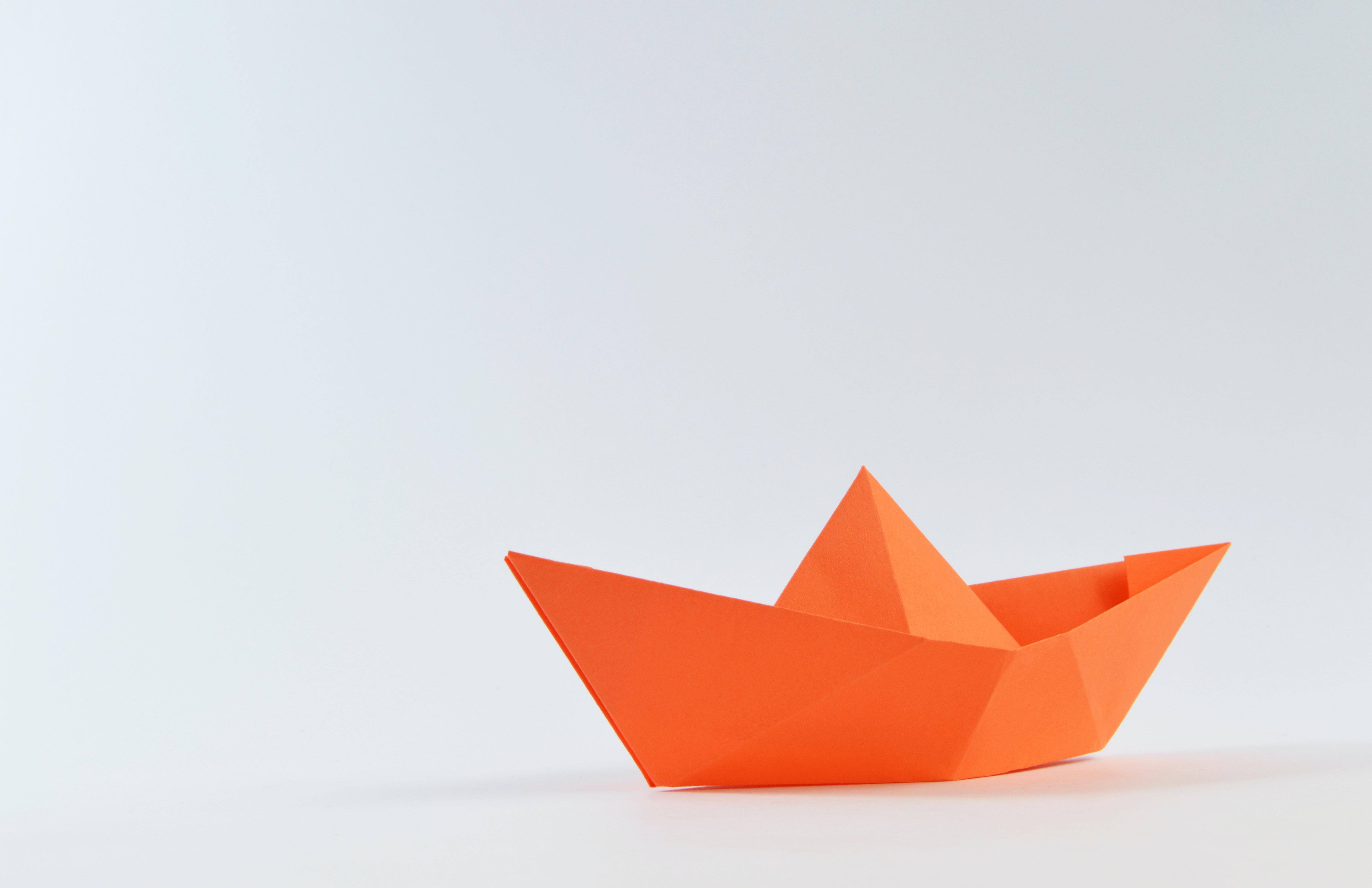 orange paper boat on white surface free stock photo