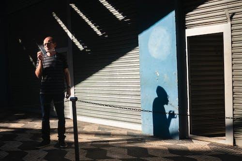 Фотография человека, курящего, стоя возле рольставни
