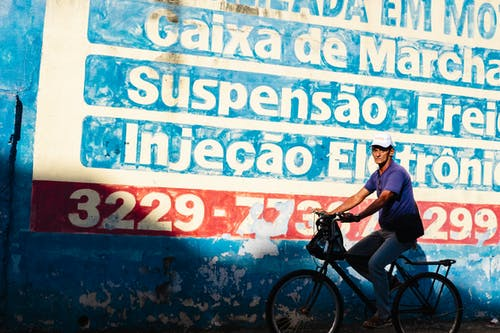 Photo of Man Riding Bicycle Near Graffiti Wall