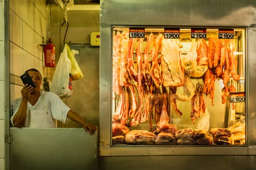 Busy ethnic butcher in white clothes speaking on phone and looking away near stand with meat in local market in soft light