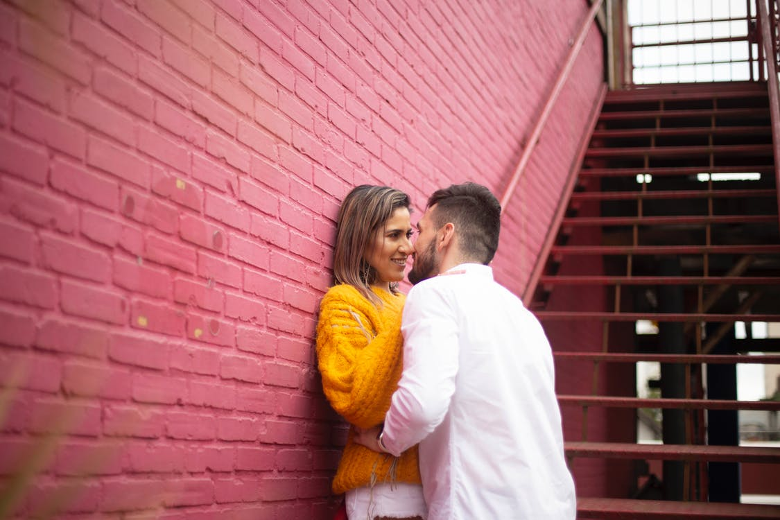 Man and Woman Standing Beside Red Brick Wall About to Kiss