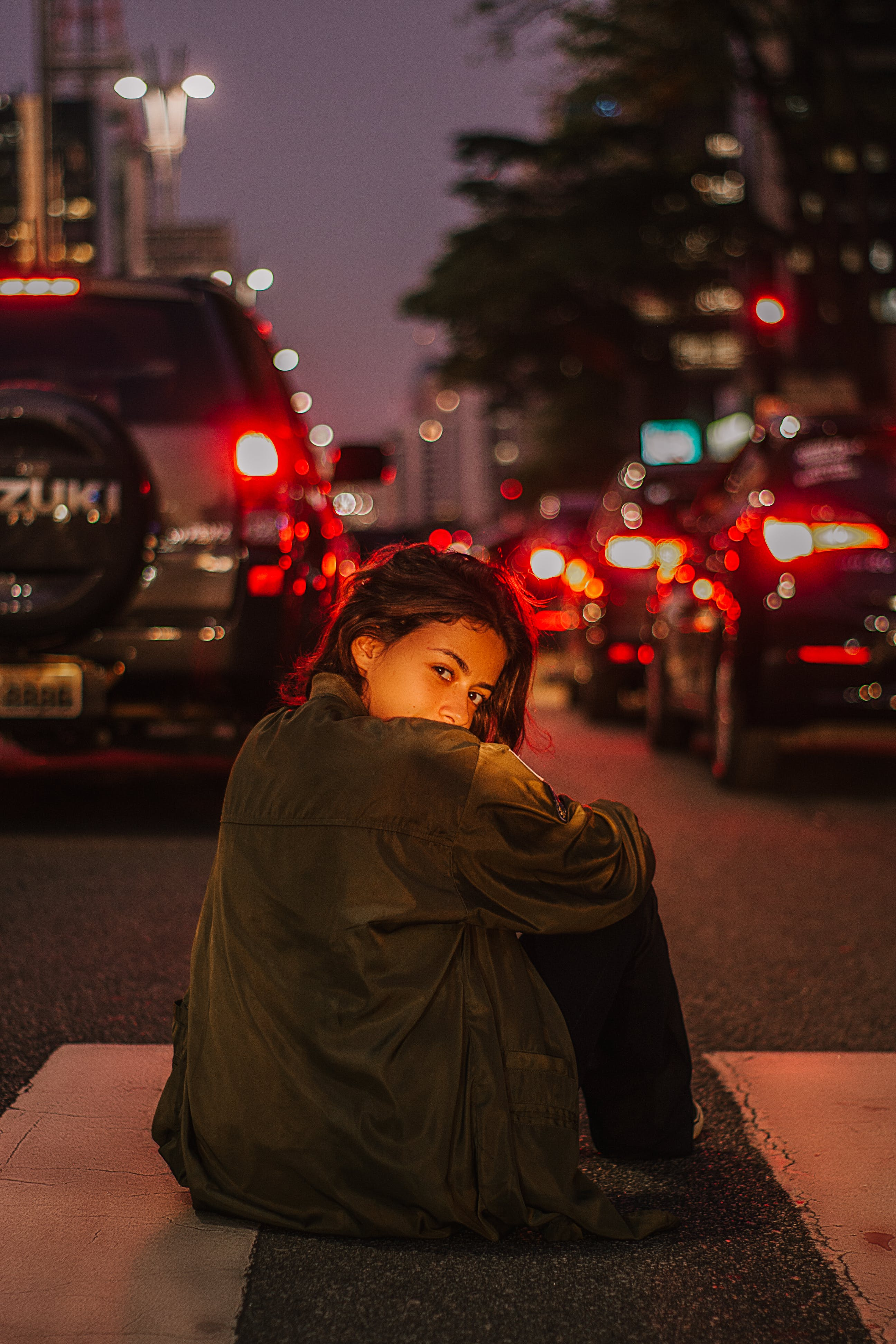 Woman Sitting on Road during Night Time