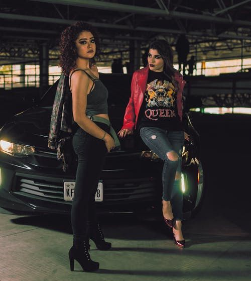 Two Woman Standing in Front of Vehicle in Building
