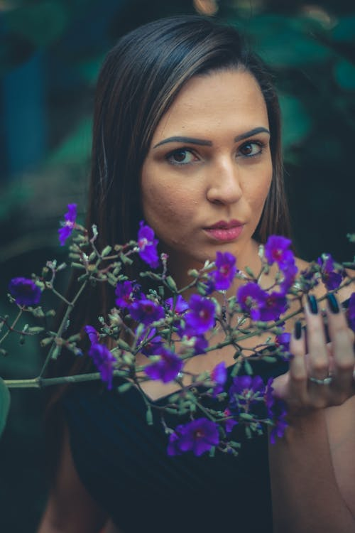 Selective Focus Photography Of Woman Behind Purple Flowers