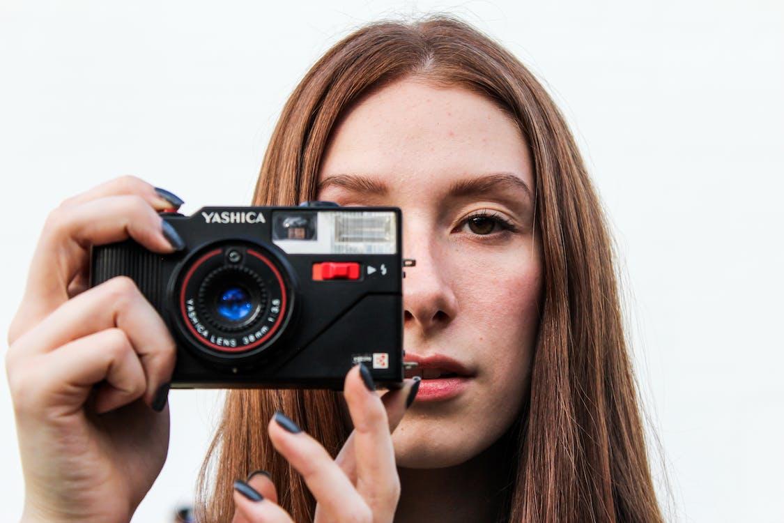 Donna Che Cattura L'immagine Usando La Macchina Fotografica Nera Di Yashica