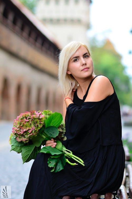 Free stock photo of beautiful, black dress, blond, cobble stones