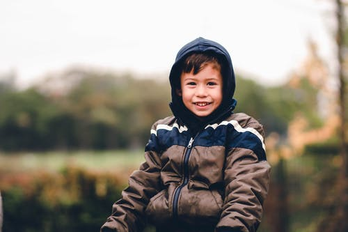 Boy Smiling and Wearing Hooded Jacket Outdoors
