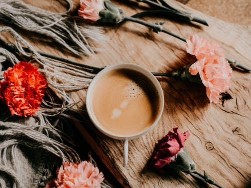 Coffee In Mug Surrounded By Flowers