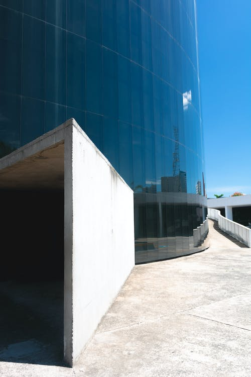 White Concrete Wall Beside Glass Building