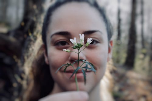 Positive woman with delicate white flower