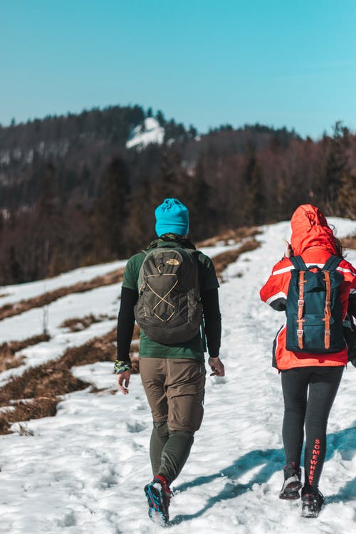 Two People Walking On Snow Trail