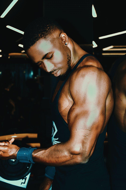A man in tank top flexing his biceps.   Photo: Pexels