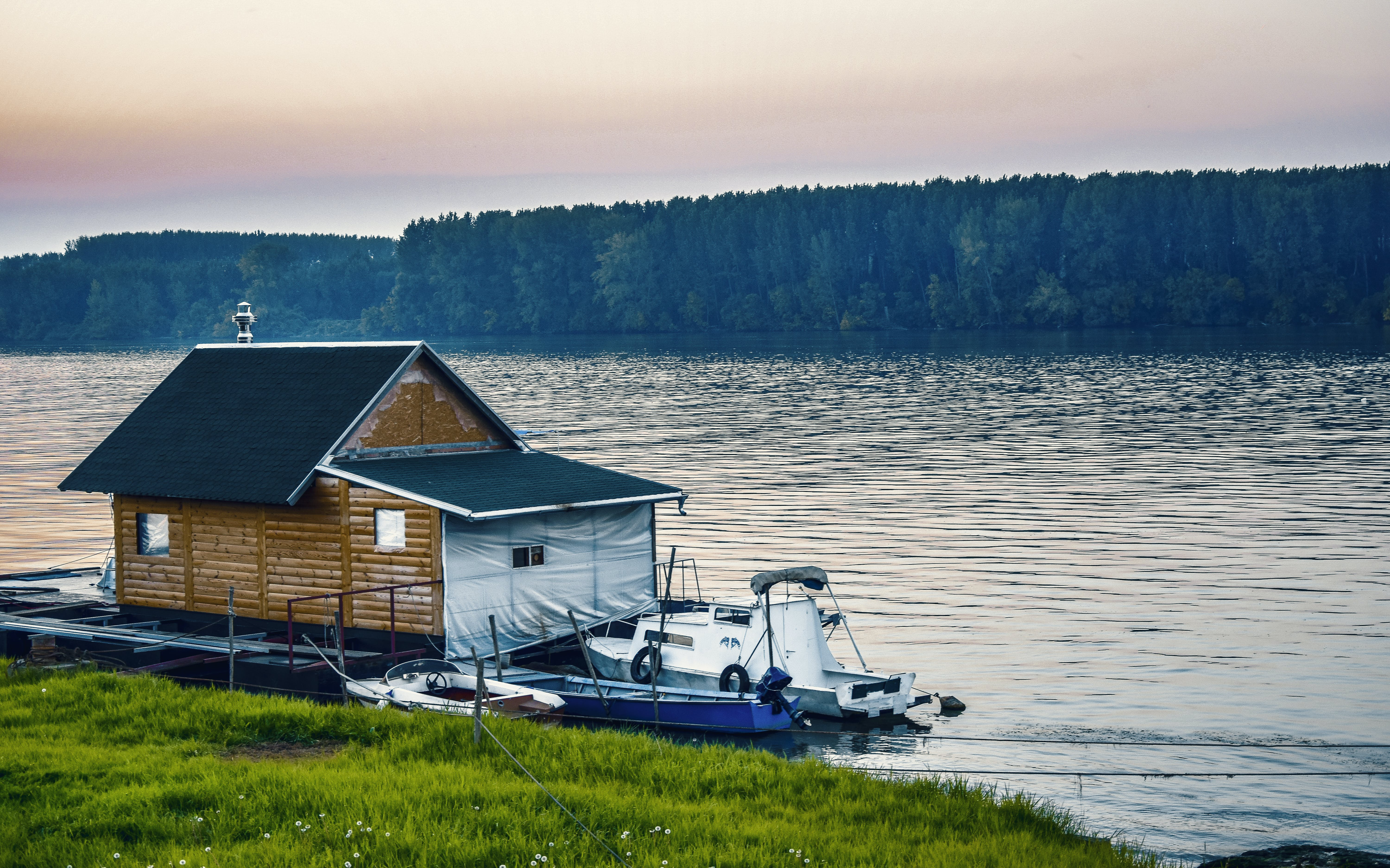 White Boat Beside Wooden House on Water Near Forest