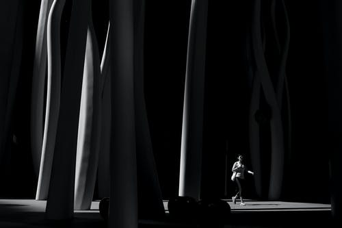 Grayscale Photo of Person Wearing Black Pants Walking Across Posts