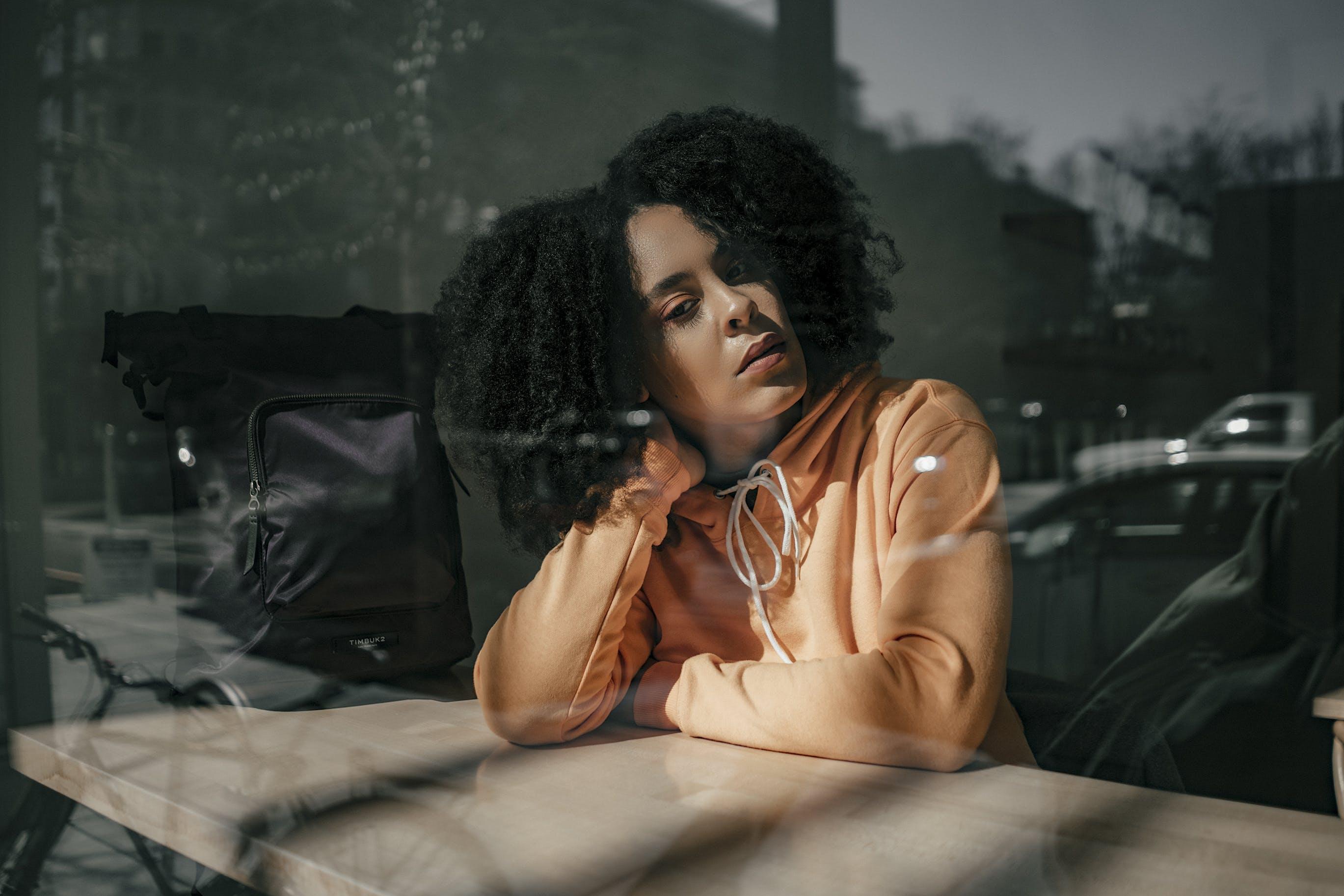 Woman Wearing Hoodie Leaning on Desk