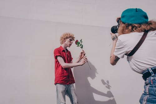 Woman Taking Photo of Man Standing and Holding Red Flower Near Wall