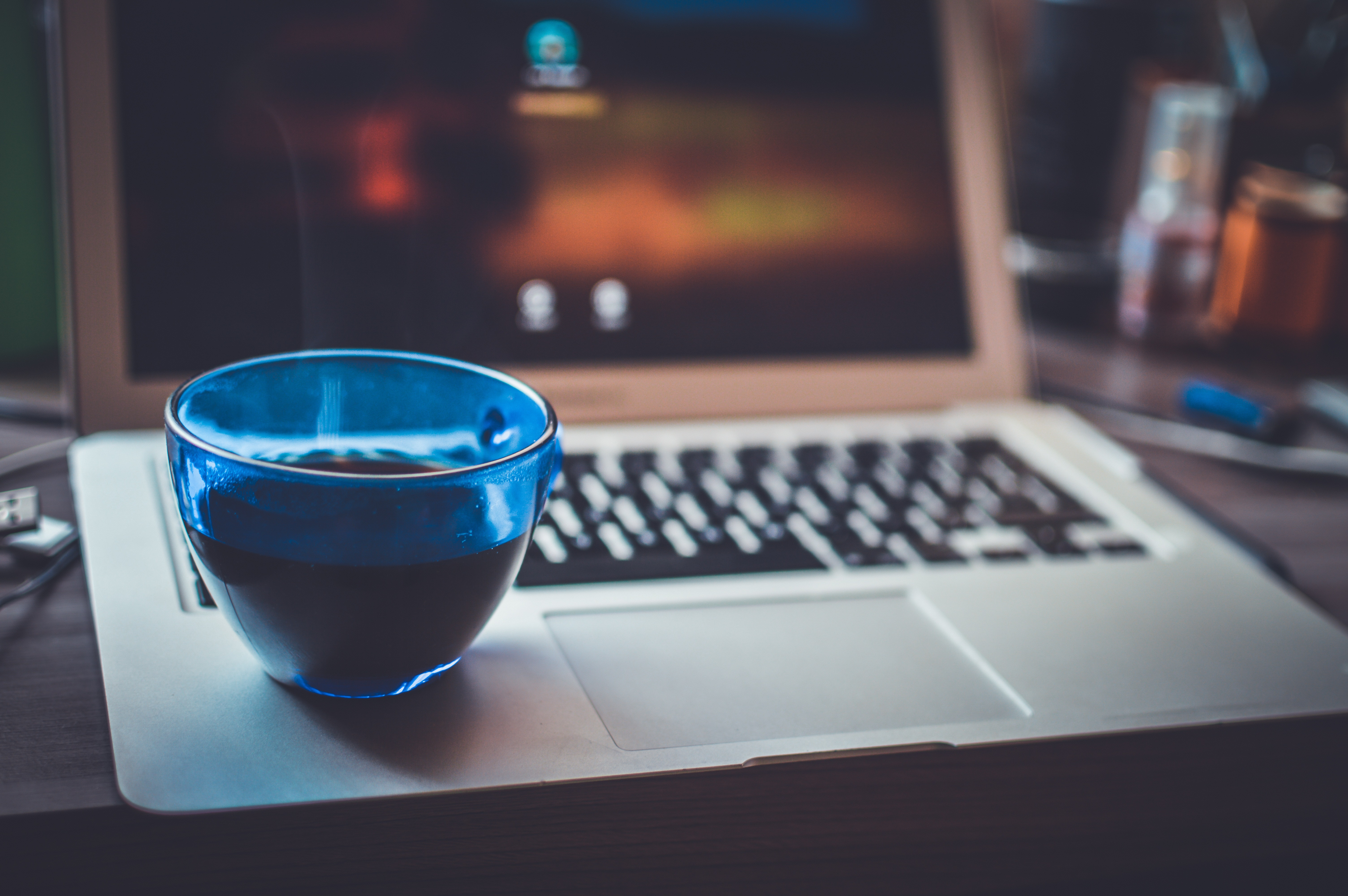 person holding white ceramic teacup in front of a macbook