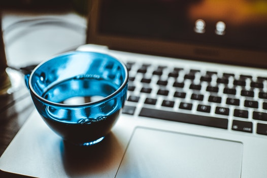Shallow Focus Photography of Blue Glass Cup on Silver Laptop Computer