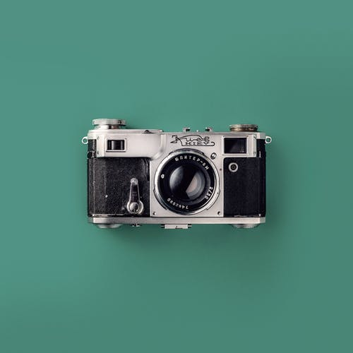Grey and Black Camera On Green Background
