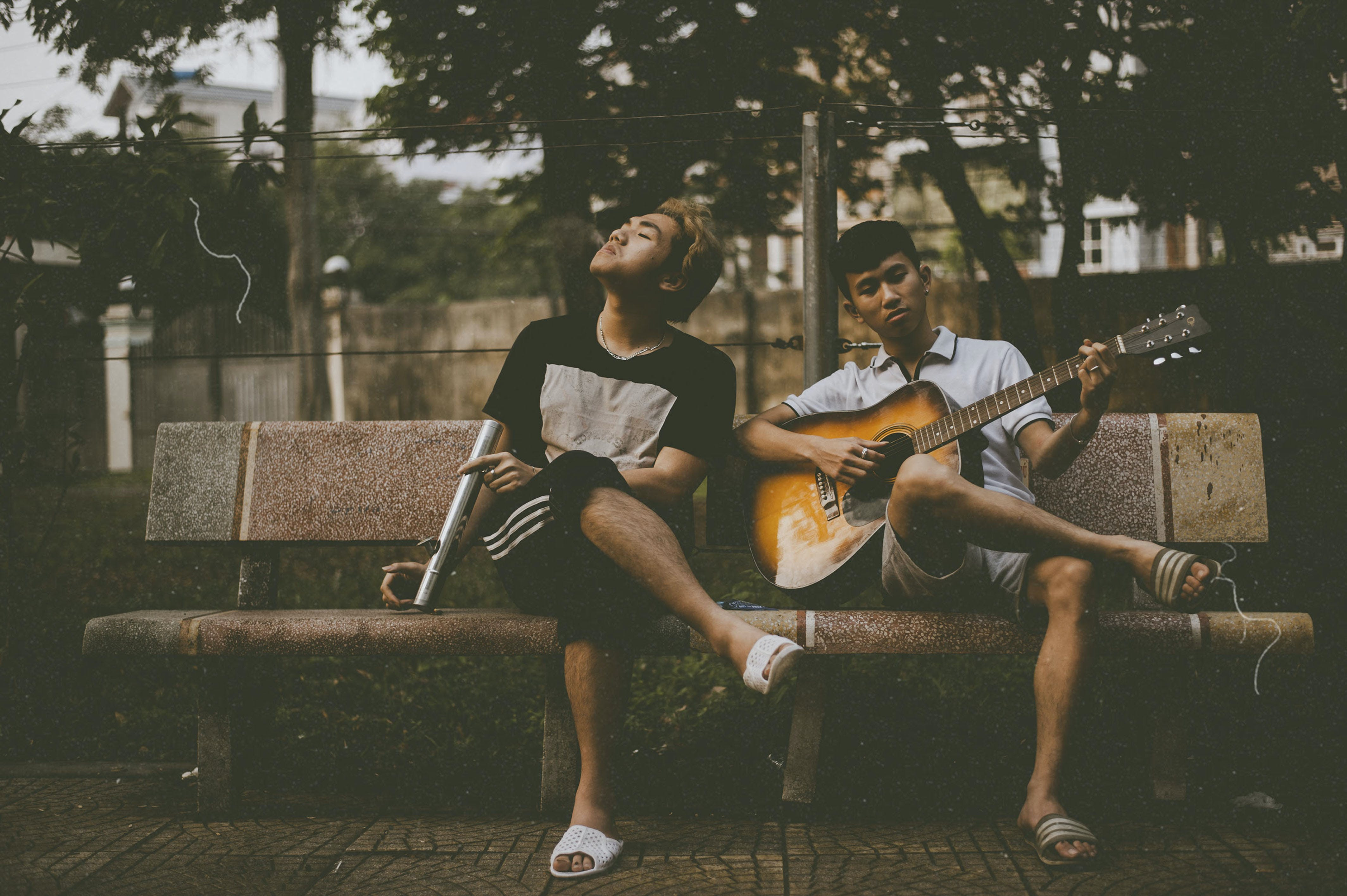 Photo of Man Playing Guitar Beside Another Man
