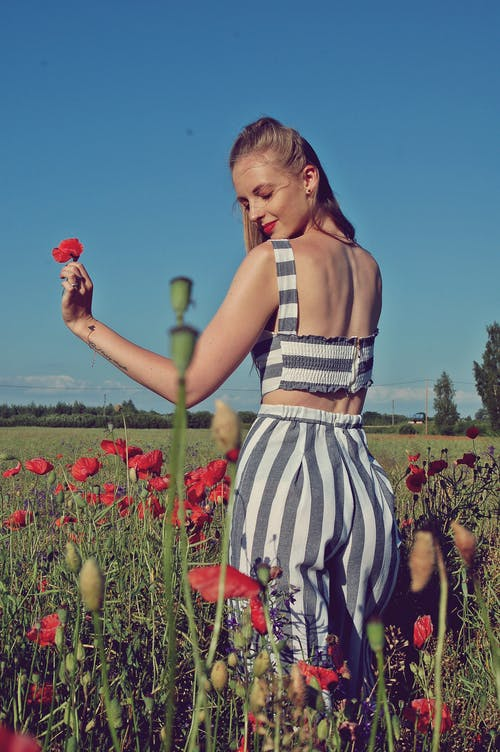 Donna Che Indossa Pantaloni A Righe Circondati Da Fiori