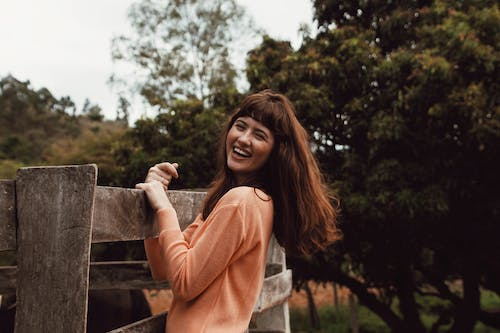 Smiling Woman Standing and Holding Wooden Fence