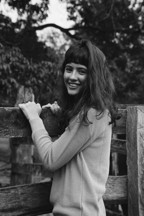 Grayscale Photo of Woman Holding Wooden Fence