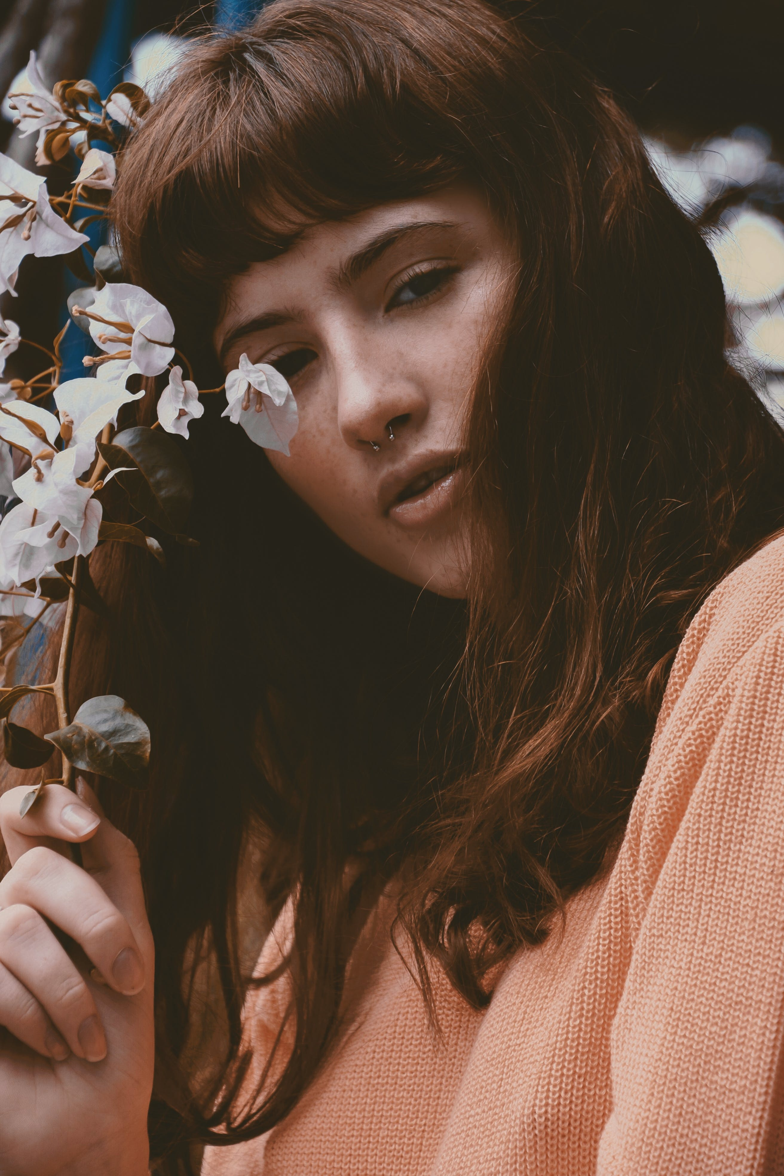 Woman Wearing Orange Sweat Shirt Holding White Flowers