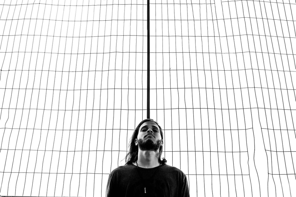 Grayscale Photography of Man Standing Near Wire Grille