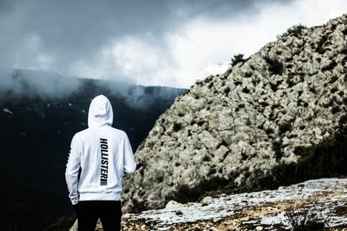 Person Wearing White Hollister Hoodie Standing Near Rock