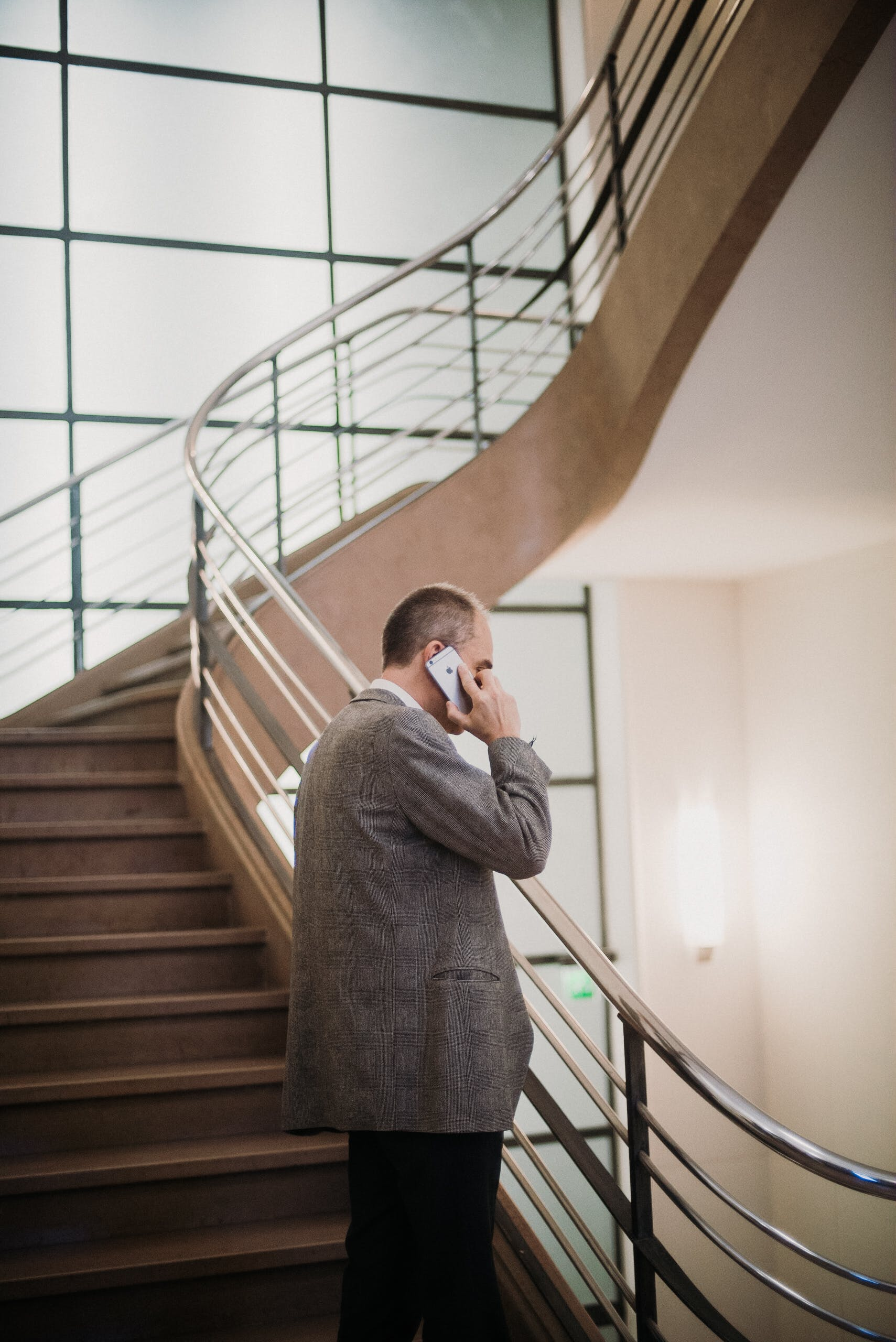 Man Listening to Smartphone While Standing on Staircase