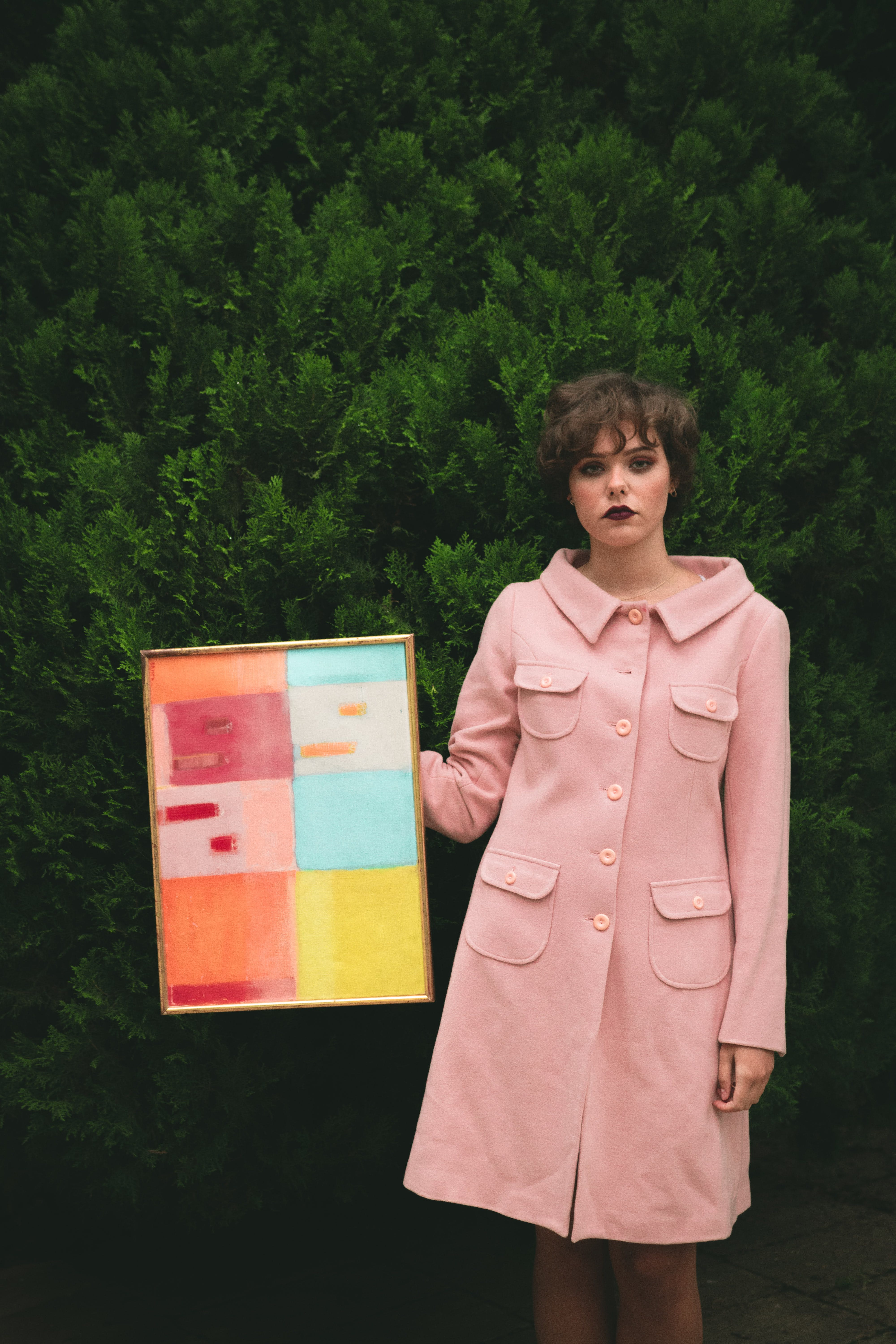 Woman Wearing Pink Button-up Coat Holding Photo Frame With Artwork