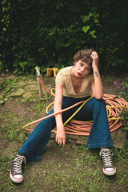 Woman Sitting on Water Hose