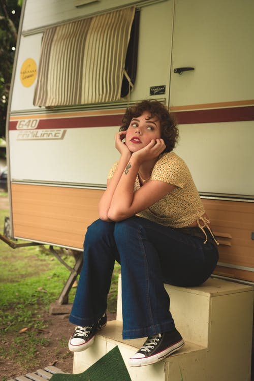 Woman Sitting on Stairs Near Travel Trailer