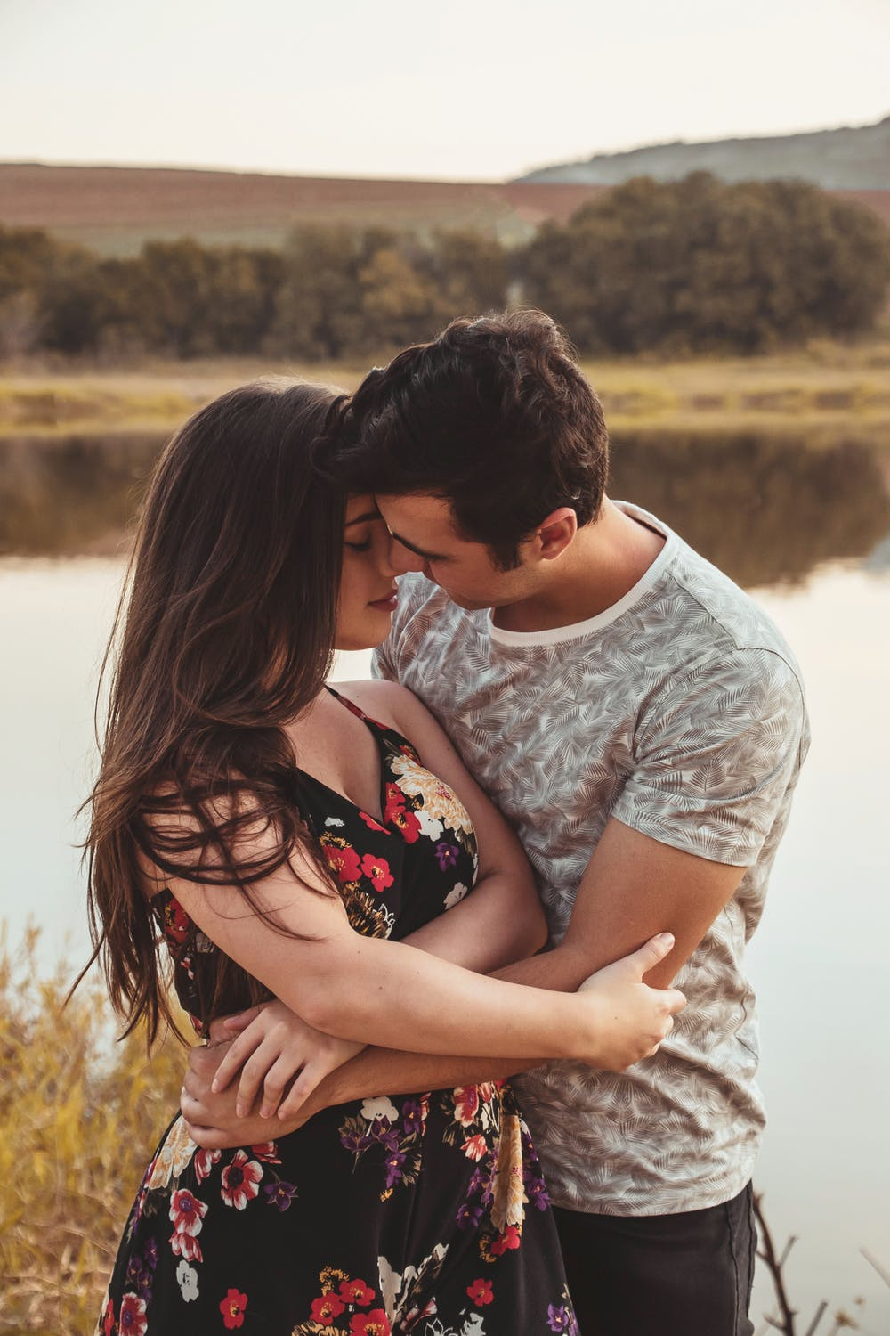 Man and woman hugging near river | Photo: Pexels