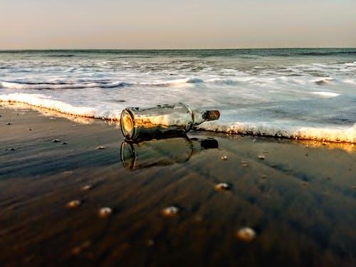 Kostenloses Stock Foto zu bierflasche, reflektierung, strand, wellen