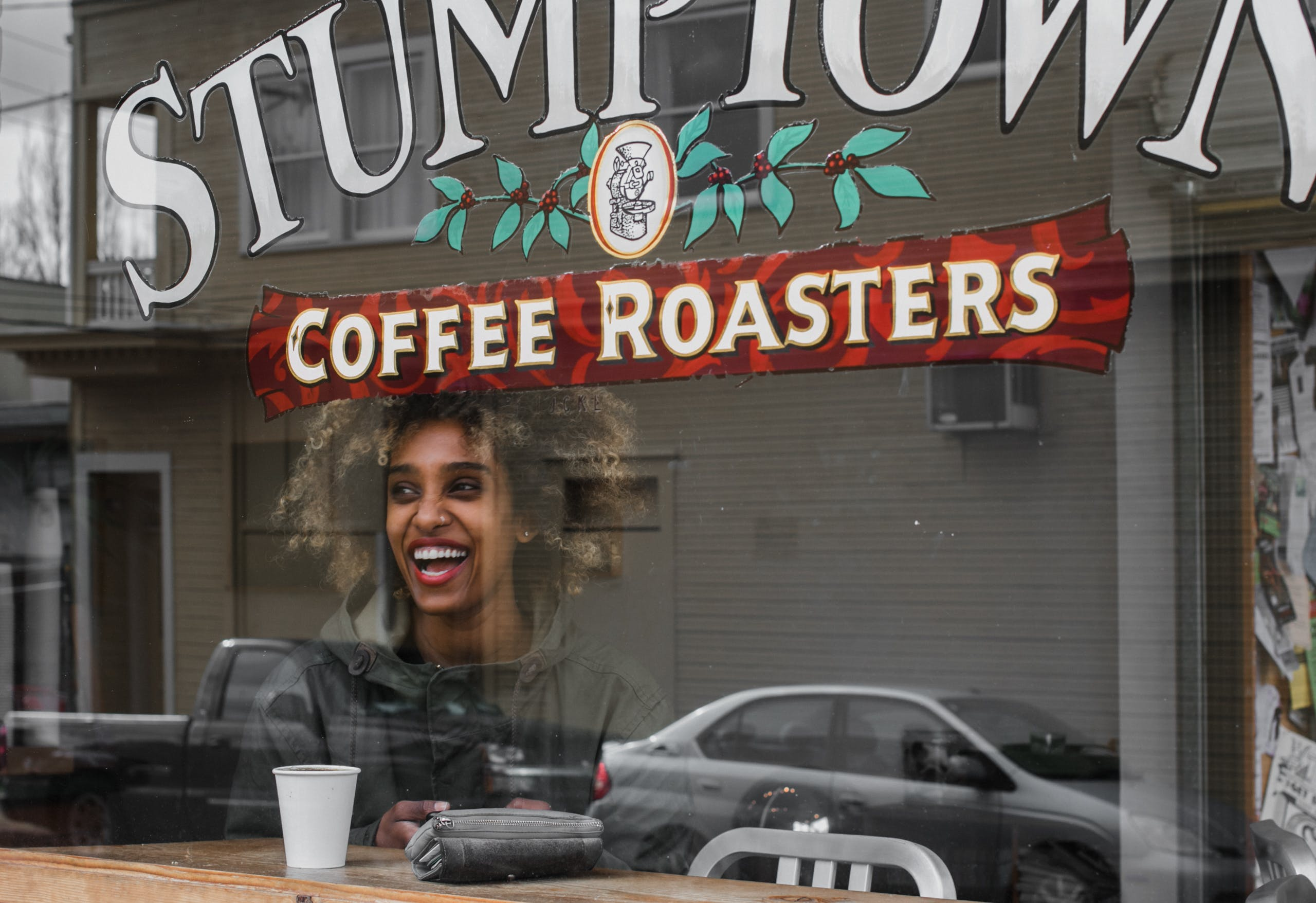 Smiling Woman Inside Coffee Roasters Cafe