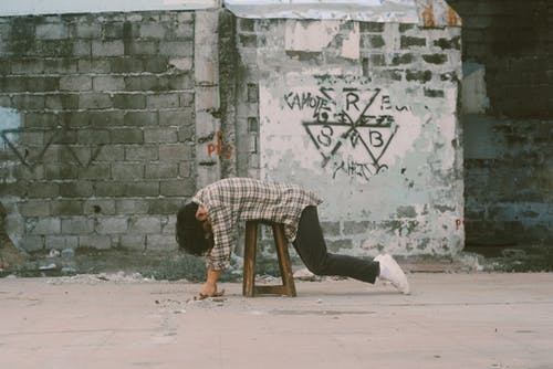 Man Lying Forward on Stool Near Wall