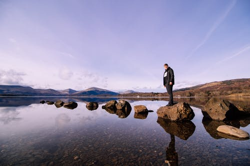 Person in Black Jacket Standing on Stone at Body of Water
