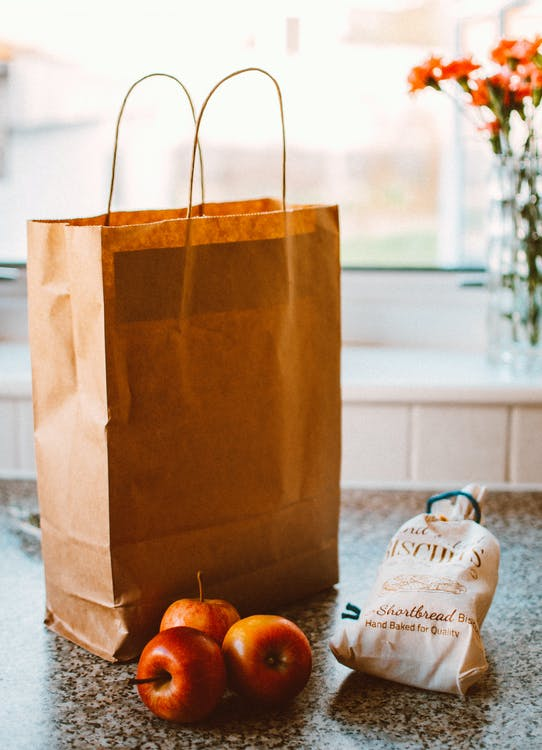 Several Apples Beside Bread Pack And Brown Paper Bag