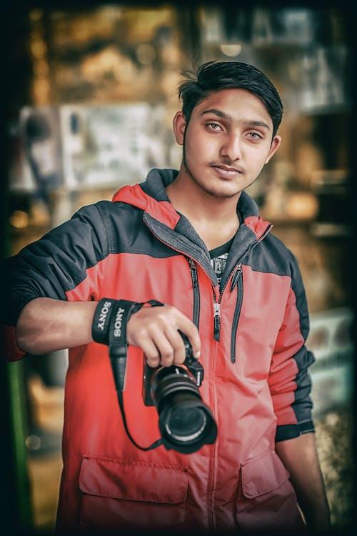 Foto profissional grátis de acreditar, câmera, fundo borrado, jaqueta preta